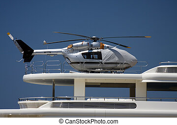 Silver helicopter on the deck of the big yacht.