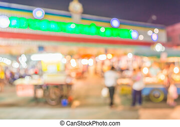 blurred image of night market and people .