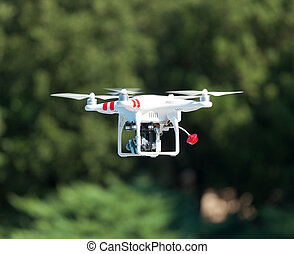 Flying helicopter with camera over the green field - White...