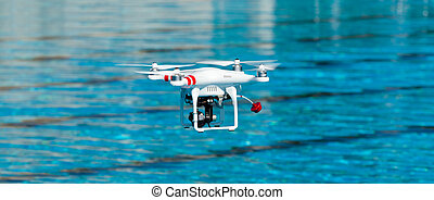 Drone quadrocopter - White drone quadcopter in flight with...