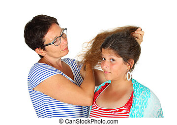 mother and daughter - woman brushing her daughters hair...