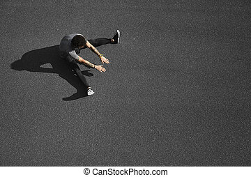 Unrecognizable runner sitting at side position. Top view jogging man taking a break during training outdoors in on black asphalt on top view. Caucasian male runner and fitness sport model after work out.