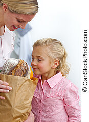 Joyful mother and her daughter unpacking grocery bag
