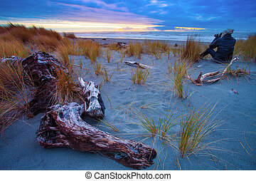 photographer on hokitika beach ,south island new zealand