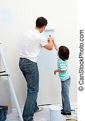 Caring father teaching his son how to paint in their new...