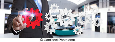 Businessman in his office moving cogwheels - Businessman...