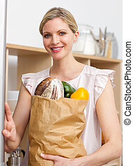 Attractive woman holding a grocery bag in the kitchen
