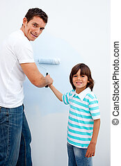 Happy father teaching his son how to paint in their new...