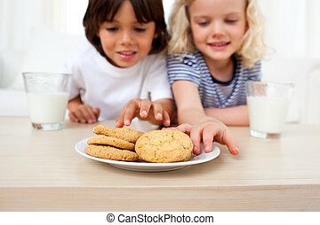 Adorable siblings eating biscuits