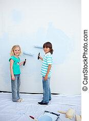 Cute siblings painting a wall