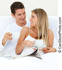 Enamoured couple drinking a cup of tea on their bed