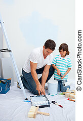 Lively Father and his son painting in their new house after...