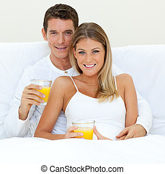 Happy couple drinking orange juice lying on their bed at...