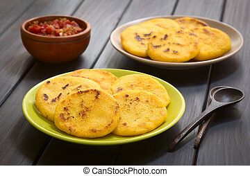 Colombian Arepa with Hogao Sauce - Two plates of arepas with...
