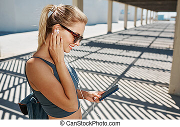 Young fitness blonde woman in sportswear listening music...