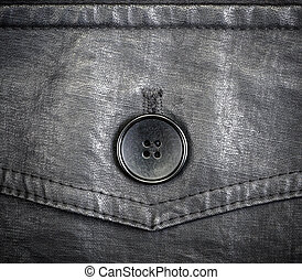 Fragment of black leather jacket with button clous-up