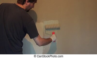 House painter renewing home interior wall, adult man...