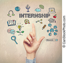 Hand pointing to Internship concept on light brown wall...