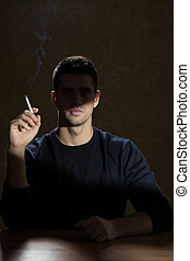 Young man smoking a cigarette - Young man addicted to...