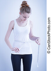 Skinny girl measuring waist - Photo of a skinny girl...