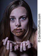 Teenager gorging on chocolate - Close up of a thin...
