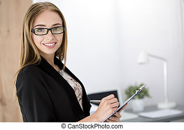 Young cheerful business woman standing with clipping board...