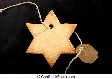 Golden fresh baked star cookie for Xmas tied with a blank...
