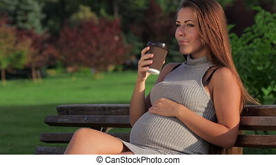 Pregnant drinking tea while sitting on a park bench. A woman...
