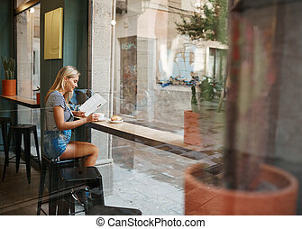 Cafe city lifestyle woman sitting in trendy urban cafe...