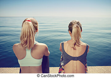 Fitness young girls relaxing after running in city. Happy sporty fit young interracial friends enjoying view of sea after jogging training outside.