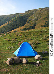 There ia a tent in the mountains - There ia a blue tent in...