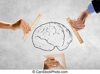Mental health - Close up of people hands measuring brain...