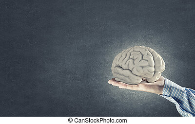Mental health - Close up of businessman hand holding brain