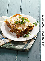 Lasagna with bolognese and bechamel on a wooden tabletop