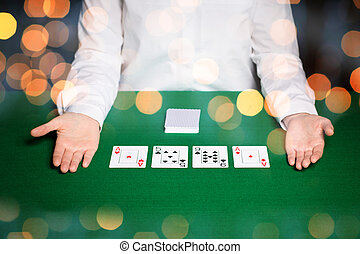 holdem dealer with playing cards over lights - casino,...
