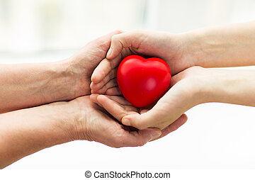 senior and young woman hands holding red heart - people,...