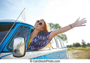 smiling young hippie woman driving minivan car - summer...