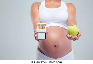Pregnant woman choosing beetwin cigarettes and apple -...
