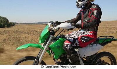 Enduro racer riding his offroad bike on road medium shot...