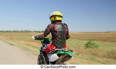 Enduro racer in motorcycle protective gear riding bike side...