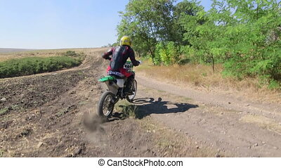 Enduro racer in motorcycle protective gear riding bike on...