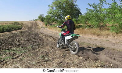 Motocross rider on his enduro bike riding away kicking up...