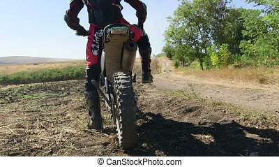 Motocross racer start riding his dirt bike kicking up dust...