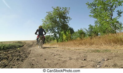 Motocross racer on enduro bike riding away rear view