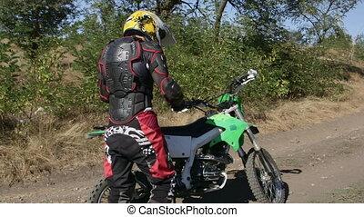 Enduro racer starting engine of his motorbike riding away on...