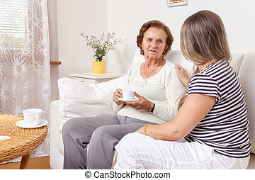 Carer having a cup of tea with an elderly woman - Carer...