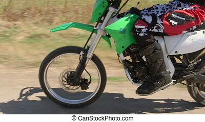 Enduro racer riding dirt bike on track, vehicle shot side...
