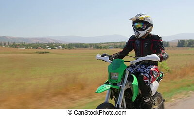 Enduro racer riding dirt bike, front side view vehicle shot
