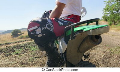 Enduro racer sitting on dirt bike looking away - Young...