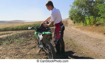 Young enduro racer puts on chest protector beside his dirt...